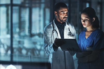 Buy stock photo Shot of two young doctors using a digital tablet late at night in a modern hospital