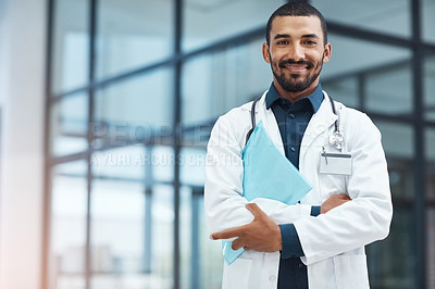 Buy stock photo Portrait of a young doctor holding a file in a modern hospital