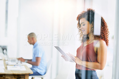 Buy stock photo Shot of a young businesswoman using a digital tablet in an office with her colleague in the background