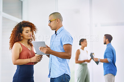 Buy stock photo Shot of two businesspeople using a digital tablet together in an office with their colleagues in the background