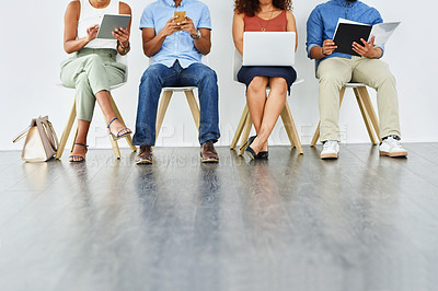 Buy stock photo Shot of a group of unrecognizable work colleagues sitting inside of a waiting room while working on their digital devices