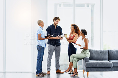 Buy stock photo Shot of a group of confident young work colleagues having a discussion together while making use of digital devices at work
