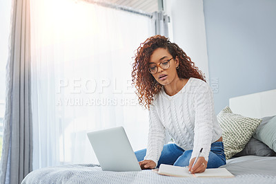 Buy stock photo Shot of a young woman writing notes while using a laptop in her bedroom at home