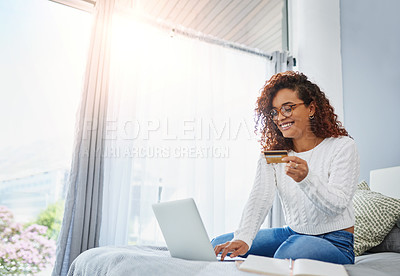 Buy stock photo Shot of a young woman using a laptop and credit card in her bedroom at home