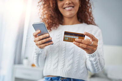 Buy stock photo Shot of a young woman using a cellphone and credit card at home