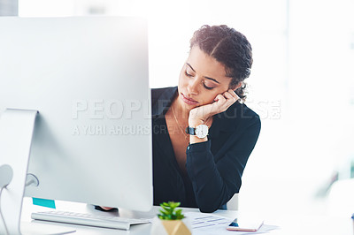 Buy stock photo Shot of a young businesswoman looking bored while working on a computer in an office