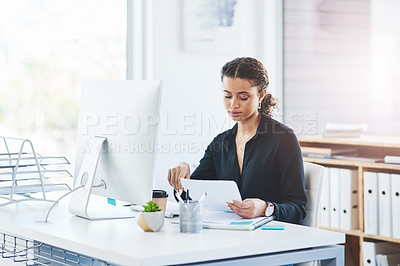 Buy stock photo Shot of a young businesswoman going through paperwork while working in an office
