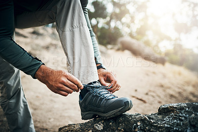 Buy stock photo Cropped shot of a unrecognizable man tying his shoe laces before going for a hike up a mountain