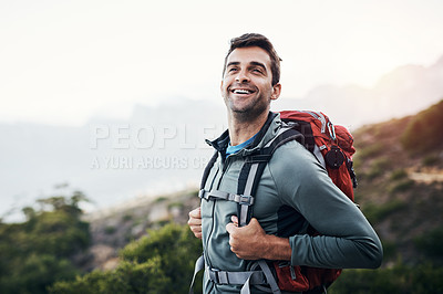 Buy stock photo Cropped shot of a cheerful young man looking into the distance while going for a hike up a mountain