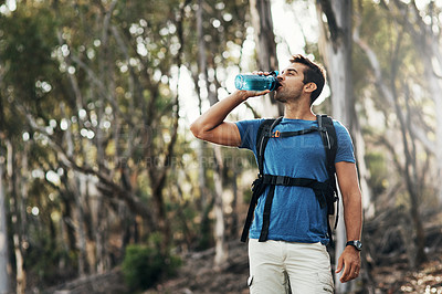 Buy stock photo Cropped shot of a carefree young man drinking water from a bottle while going for a hike up a mountain