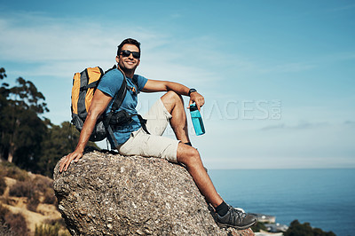 Buy stock photo Portrait of a carefree young man taking a quick break from hiking up a mountain during the day