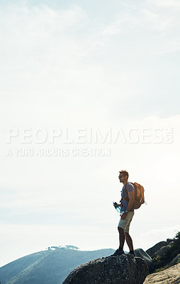 Buy stock photo Cropped shot of a carefree young man standing on top of a mountain after a day of hiking