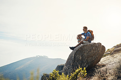 Buy stock photo Cropped shot of a carefree young man sitting on top of a mountain after a day of hiking