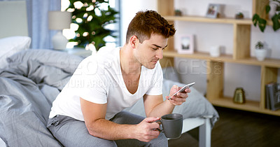 Buy stock photo Cropped shot of a handsome young man using his smartphone while sitting on his bed at home