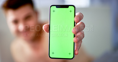 Buy stock photo Cropped shot of an unrecognizable young man holding up his smartphone at home