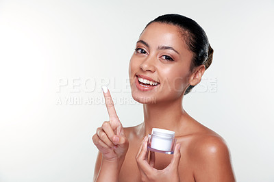Buy stock photo Shot of a beautiful young woman applying moisturiser to her face against a studio background