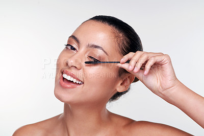 Buy stock photo Shot of a beautiful young woman applying mascara  against a studio background