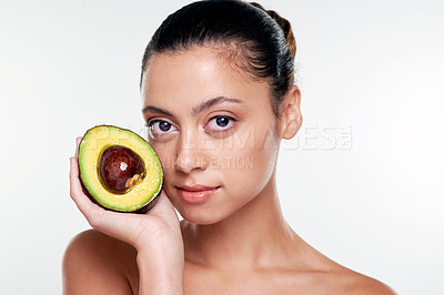 Buy stock photo Shot of a beautiful young woman holding an avocado against a studio background