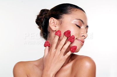 Buy stock photo Shot of a beautiful young woman with raspberries on her fingers against a studio background