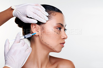 Buy stock photo Shot of a beautiful young woman getting her face injected by gloved hands against a studio background