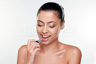 Buy stock photo Shot of a beautiful young woman applying lipstick  against a studio background