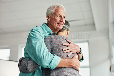 Buy stock photo Shot of an affectionate senior couple hugging each other inside their home