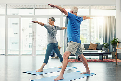 Buy stock photo Full length shot of an active senior couple exercising together inside their home