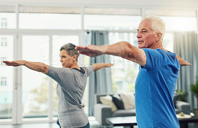 Buy stock photo Shot of an active senior couple exercising together inside their home