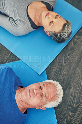 Buy stock photo High angle shot of a senior couple lying down on the floor while exercising together at home