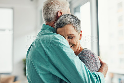 Buy stock photo Shot of an affectionate senior couple hugging each other at home