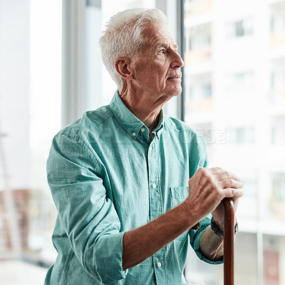 Buy stock photo Shot of a senior man looking out the window and holding his while holding his walking stick at home