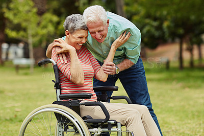 Buy stock photo Shot of a cheerful senior man embracing his wheelchair bound wife in the park