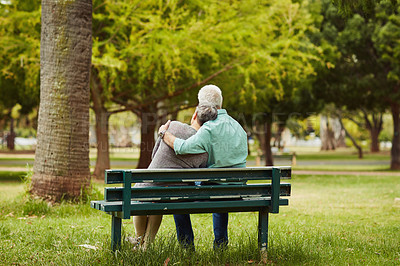 Buy stock photo Rearview shot of an affectionate senior couple sitting on a bench in the park