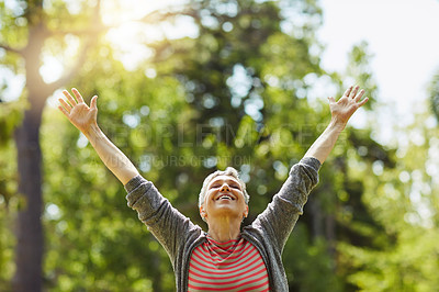 Buy stock photo Shot of a cheerful senior woman posing with her arms raised outdoors