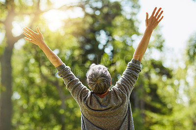 Buy stock photo Rearview shot of a cheerful senior woman posing with her arms raised outdoors