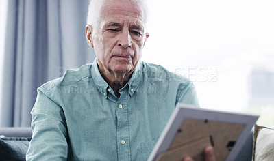 Buy stock photo Shot of a thoughtful senior man looking at a picture frame at home