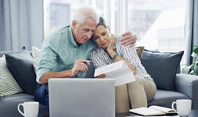 Buy stock photo Shot of a senior couple going through paperwork at home