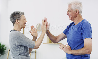 Buy stock photo Shot of a senior couple giving each other a high five while doing yoga together at home