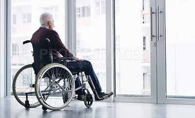 Buy stock photo Shot of a senior woman in a wheelchair looking thoughtfully out of a window at home