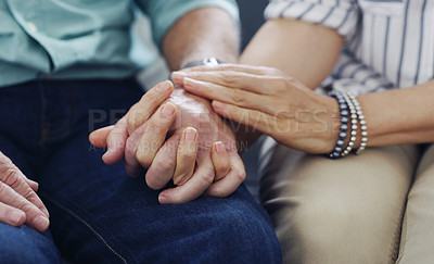Buy stock photo Shot of an unrecognisable senior couple holding hands at home