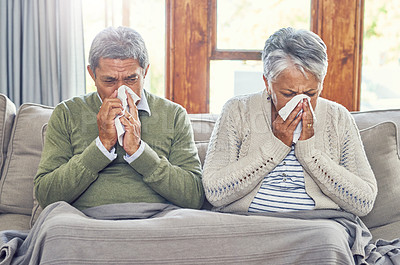 Buy stock photo Shot of a sickly senior couple each blowing their nose with a tissue while sitting on a couch at home