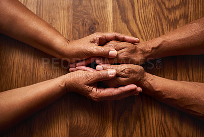 Buy stock photo High angle shot of an unrecognizable senior couple holding hands together over a wooden table at home