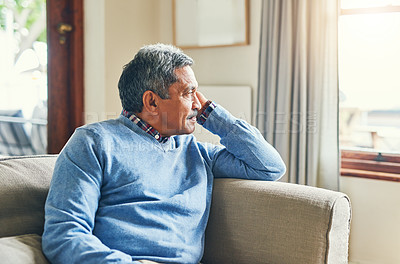 Buy stock photo Shot of a senior man looking very thoughtful while relaxing on a sofa at home