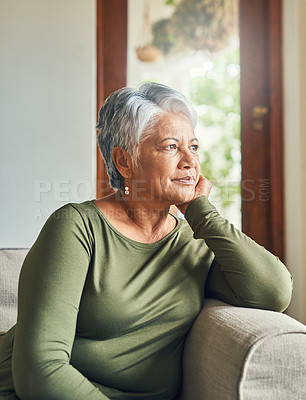 Buy stock photo Shot of a beautiful senior woman looking very thoughtful while relaxing on a sofa at home