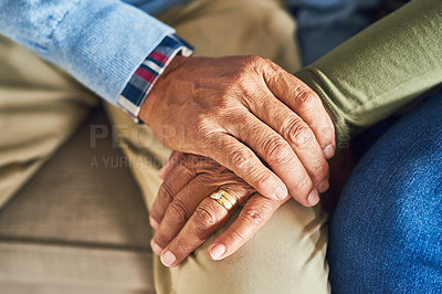 Buy stock photo Shot of an unrecognizable senior couple holding hands together while sitting on a couch at home