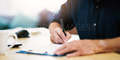 Buy stock photo Shot of an unrecognizable businessman writing a few notes on a clipboard in his office