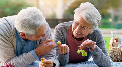 Buy stock photo Cropped shot of a cheerful elderly couple eating grapes together outside in a park