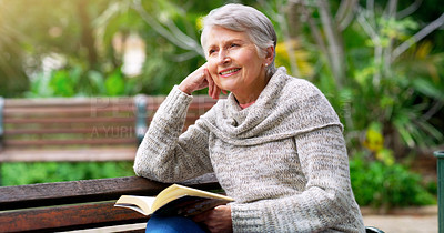 Buy stock photo Cropped shot of a cheerful elderly woman reading a book by herself outside in a park