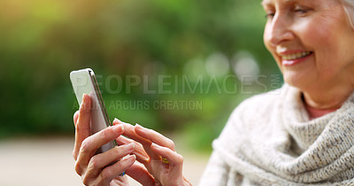 Buy stock photo Cropped shot of a cheerful elderly woman texting on her cellphone while being seated on a bench outside in a park
