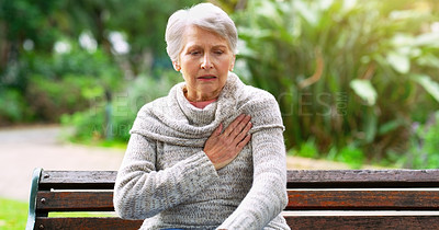 Buy stock photo Cropped shot of a stressed out elderly woman seated on a bench and holding her chest in discomfort outside in a park